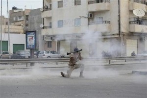 A member of the Libyan army with a weapon is seen amidst smoke during clashes between members of Islamist militant group Ansar al-Sharia and a Libyan army Special Forces unit in the Ras Obeida area in Benghazi November 25, 2013.