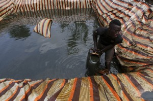 A man named Godswill collects crude oil from a small storage pit filled with oil, which is waiting to be refined at an illegal refinery site near the river Nun in Nigeria's oil state of Bayelsa, on November 27, 2012.