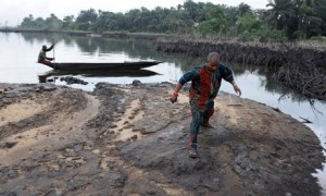 A man walks on slippery spilled crude oil on the shores of the Niger Delta swamps of Bodo, a village in Niger's oil-producing Ogoniland.
