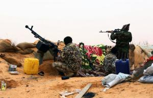 Fighters from the Fajr Libya (Libya Dawn) militia hold a position during clashes with forces loyal to Libya's internationally recognized government near the Wetia military air base, as they fight for control of the area some 170 kilometres west of the capital Tripoli on December 29, 2014. AFP/Mahmud Turkia